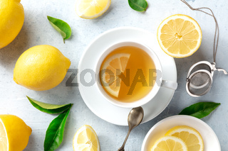 Lemon tea in a cup, overhead flat lay shot with organic lemons and green leaves