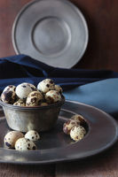 Pewter plates with quail eggs on wood table