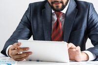 Businessman using tablet computer at office desk