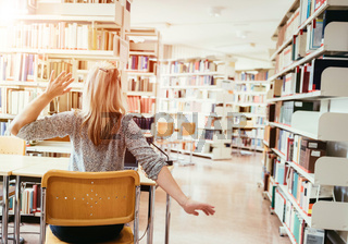 Learning for exams: tired female student in the university library, pile of books