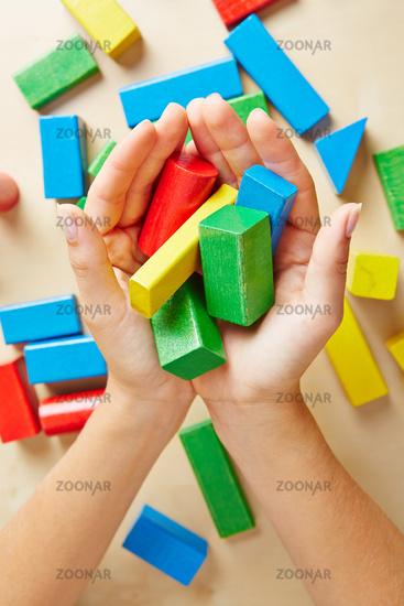 Zwei Hände halten bunte Bausteine