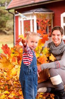 Mutter und Tochter spielen im Herbstlaub