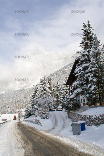 A snow-covered road in the shadow of the Dolomites