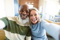 Happy senior diverse couple in living room sitting on sofa, making video call