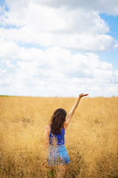 Portrait of a young beautiful brunette woman in a blue T-shirt and denim shorts stands in the middle of the field, exposing her face to the sun on the background of a summer day outdoors.