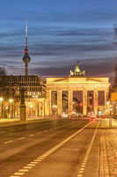 The famous Brandenburg Gate in Berlin with the Television Tower at twilight