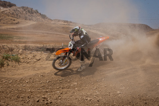 Unrecognized athlete riding a sports motorbike on a motocross racing event. Extreme sports high speed.
