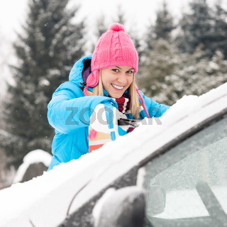 Woman cleaning car windshield of snow winter