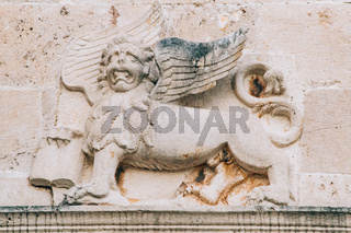 A bas-relief on the wall depicting a mythical lion with wings and a book in its paws.