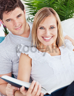 portrait of a caucasian couple reading a book sitting in the living-room