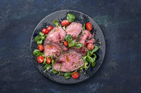 Modern style traditional Commonwealth Sunday roast with sliced cold cuts roast beef served with tomatoes and corn lettuce as top view on a Nordic design plate with copy space