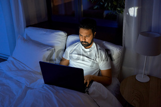 indian man with laptop in bed at home at night