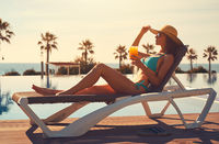 Woman in bikini drinks cocktail sunbathing on deckchair near pool