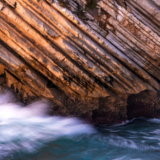 Beautiful schist cliff details in Baleal island with ocean waves crashing in Peniche, Portugal