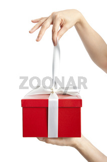 hand holding ribbon and open gift box