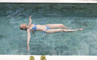 The happy slender young woman lies on a water surface in the pool and has a rest