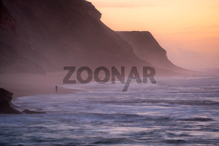 Fishermen in Santa Cruz beach at sunset, in Portugal