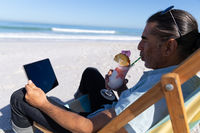 Senior Caucasian man sitting on a deck chair and using a digital tablet at the beach