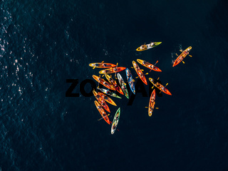 A group of kayakers gathered their kayaks in a heap in sea. Group swim in pairs kayaks. Concept banner travel. Aerial top view.