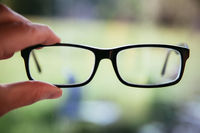 Sense concept: holding black glasses outdoors