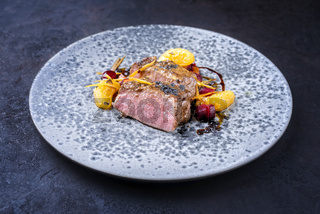 Modern style traditional roasted dry aged veal tenderloin with tangerine and braised winter root vegetable in jus and served as close-up in a design plate