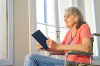 Seniorin im Rollstuhl nach einem Schlaganfall liest ein Buch