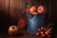 apples in a garden jug on a dark wooden background in a rustic style