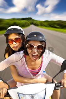 two girls riding scooter on the road