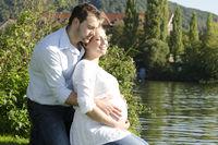 Schwangerschaft: Glückliches Paar in der Natur lächelt