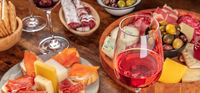 Gourmet wine appetizers panorama with a glass of rose wine, a cheese board