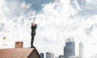 Engineer man standing on roof and looking in binoculars. Mixed m