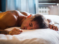Handsome shirtless young man sleeping in bed