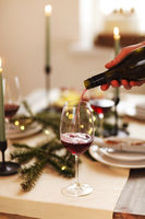 Candles and wine on Christmas table. Man serving wine during dinner