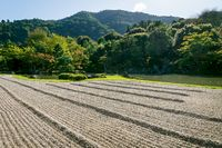 Stone zen garden with with raked gravel along pond at Sogenchi garden at Tenryu-ji temple, Japan
