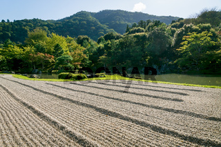 Stone zen garden with with raked gravel along pond at Sogenchi garden at Tenryu-ji temple in Kyoto, Japan