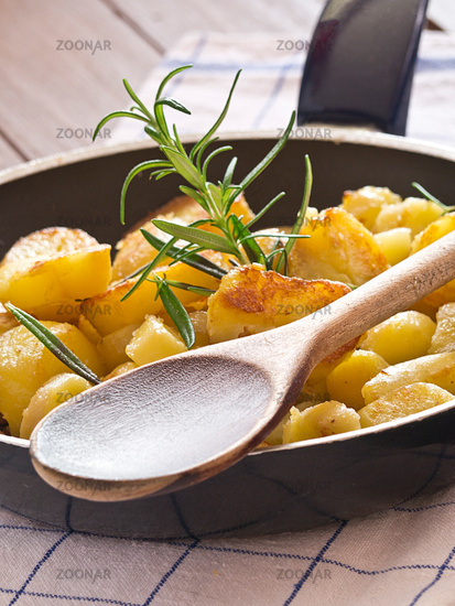 Fried potatoes in a saucepan with Rosemary