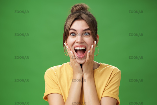 Portrait of happy delighted and surprised young feminine girl in yellow t-shirt pressing hands to cheeks from amazement and joy smiling broadly reacting to astonishing news over green background