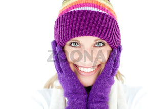 Radiant young woman with cap and gloves in the winter smiling at the camera against a white background