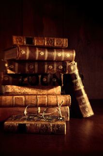 Stack of old books with reading glasses