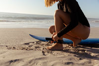 Mid section of woman preparing for surfing on the beach