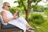 Freelancer Frau beim Videochat am Laptop im Garten