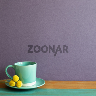 Mint coffee cup on wooden table. purple wall background