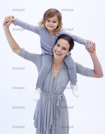 Mother giving her daughter piggyback ride against white