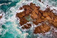 Aerial view of blue ocean surrounding  etched rocks and boulders