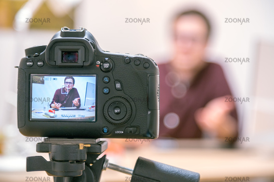Video blogger at home: Camera on tripod is filming a young man sitting on his working place