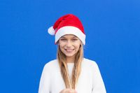 Pleased girl in white sweater and Santa hat holding pigtails smiling away isolated on blue background