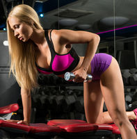 Gorgeous blonde training with dumbels in a gym
