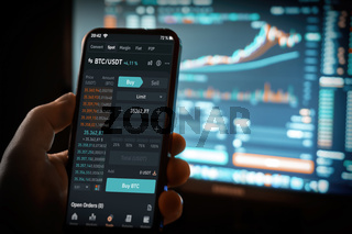 Illustrative Daytrader working from home using Binance app on Computer screen and phone with charts