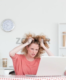 Attractive blonde female being angry while relaxing with her laptop in the kitchen