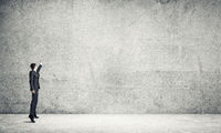 Businessman draw on concrete wall
